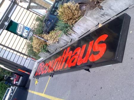 Schild Discounthaus am Boden